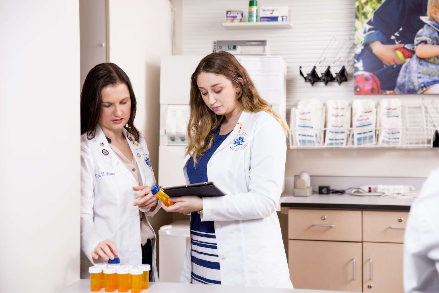 Student pharmacists consults with mentor in pharmacy